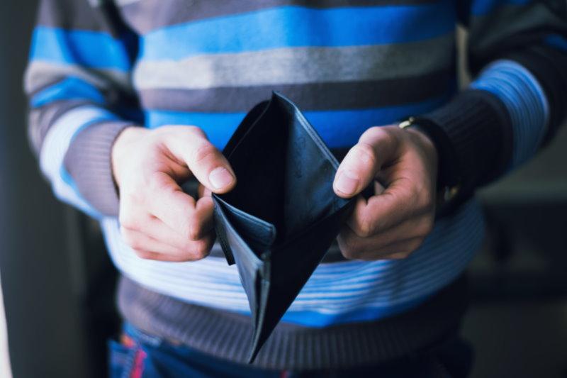 man in striped blue sweater holding open an empty wallet