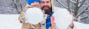 father and son holding snow balls
