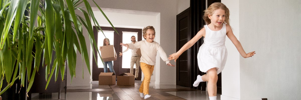 parents with moving boxes and children running through new home