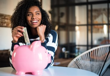 Young woman putting money into a piggy bank and smiling