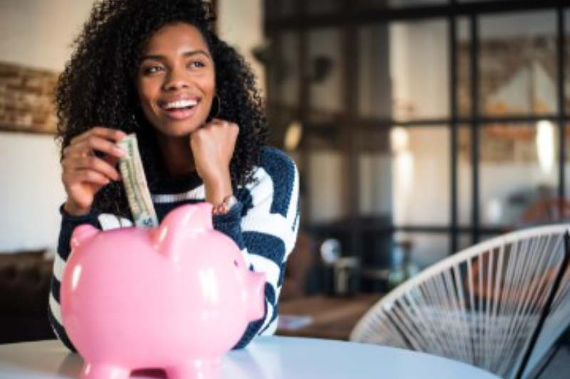 oung woman putting money into a piggy bank and smiling