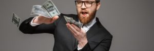 man in suit with beard making it rain with $100 bills