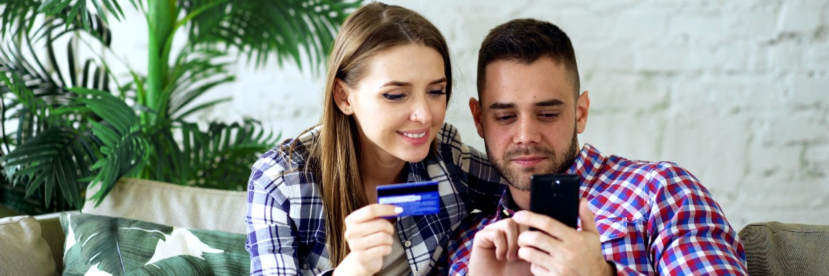 young couple entering credit card information on a mobile phone