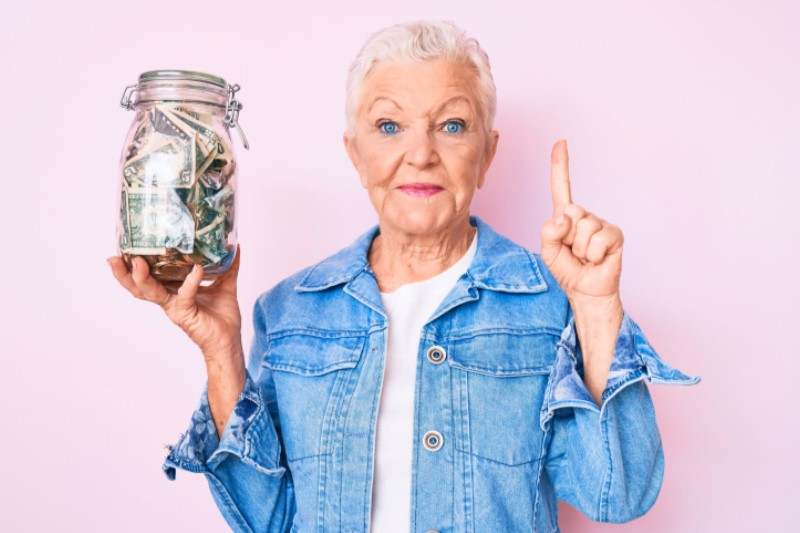 Grandma with jean jacket holding jar of money
