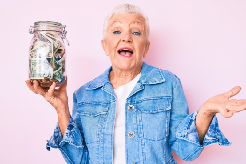 Hip Grandmother in jean jacket holding a jar of money