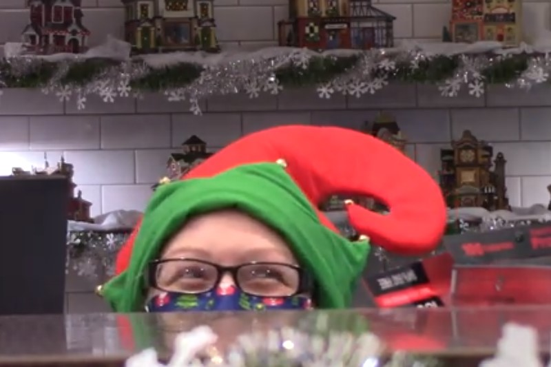 Employee dressed as elf looking over the counter
